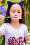 Happy little girl playing with soap bubbles on a summer nature, wearing a blue ears tiger accessories over her head in a Stock Photos