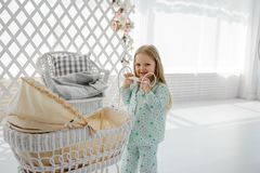 Happy little girl is playing with a stroller in the children`s room. Little girl is playing with a stroller. Baby stock image