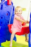 Happy little girl playing on swing Stock Image