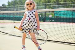 Happy little girl playing tennis. Summer sport Stock Photos