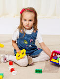Happy little girl playing with toys Stock Photos