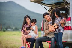 Happy little girl playing ukulele with asian family sitting in the car for enjoying road trip and summer vacation stock photos