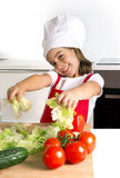 Happy little girl playing with vegetables at home kitchen in apron and cook hat Stock Images