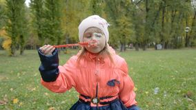Happy little girl playing wit soap bubbles in autumn park