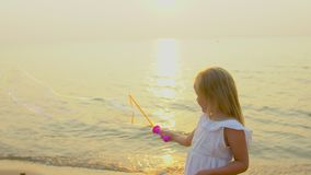 Happy Little Girl Playing wit Soap Bubbles outdoor on the beach during beautiful sunset happy vacation time in slow