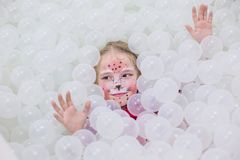 Happy little girl in a playroom in a white room. With aqua make-up on her face stock image