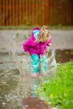 Happy little girl plays in a puddle Stock Photography