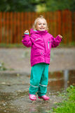 Happy little girl plays in a puddle Royalty Free Stock Image