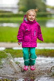 Happy little girl plays in a puddle Royalty Free Stock Photos