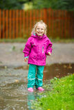 Happy little girl plays in a puddle Royalty Free Stock Photo