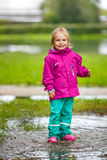 Happy little girl plays in a puddle Stock Image