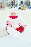 Happy little girl plays with snow on playground Stock Photo