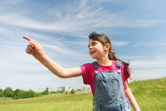 Happy little girl pointing finger on summer field Royalty Free Stock Images