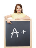Happy little girl pointing finger to blackboard Stock Images