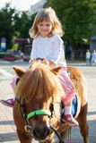 Happy little girl on a pony Stock Images