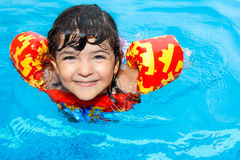 Happy little girl in pool. A cute little girl with hazel eyes, wearing an inflatable life vest, having fun in swimming pool Stock Photo