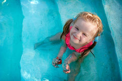Happy little girl in a pool. With big smile Stock Image