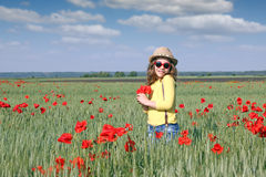 Happy little girl with poppy flower. Spring season Royalty Free Stock Images