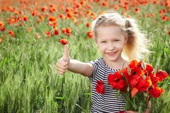 Happy little girl on poppy meadow giving thumb up Royalty Free Stock Images