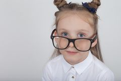 Happy little girl portrait, wearing white blouse and black frame eyeglasses, standing against white wooden background. Back to sch stock images