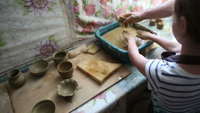 Happy little girl at a pottery art workshop, washing her dirty hands. After creating clay bowl on a sculpting wheel. Senior potter helps the child. Mentoring stock video
