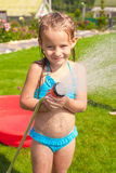 Happy little girl pouring water from a hose and Stock Photos