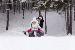 Happy little girl prepares to slide down a snowy hill. Royalty Free Stock Photo