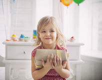 Happy little girl with present celebrating her birthday Stock Photography