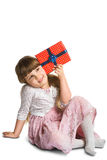 Happy little girl put gift box to the ear Stock Photography