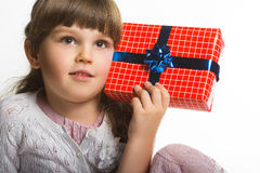 Happy little girl put gift box to the ear  isolated on white background Stock Image