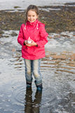 Happy little girl in rain boots playing with ships in the spring creek standing in water Stock Photos