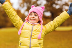 Happy little girl with raised hands outdoors. Autumn, childhood, happiness and people concept - happy little girl with raised hands having fun outdoors Royalty Free Stock Photos