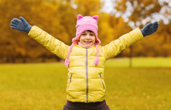 Happy little girl with raised hands outdoors. Autumn, childhood, happiness and people concept - happy little girl with raised hands having fun outdoors Royalty Free Stock Photography