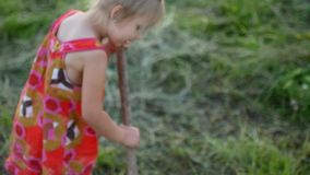 Happy little girl with rake at the countryside on a summer day stock video footage