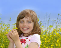 Happy little girl with rapeseed Stock Images