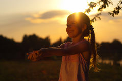 Happy little girl reaching out. Into the sunset Royalty Free Stock Photos