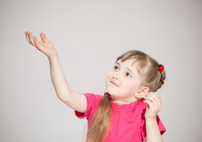 Happy little girl reaching out her palm and catching something Stock Images