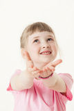 Happy little girl reaching out her palms and catching something Stock Photo