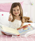 Happy little girl reading in bed with thumb up Stock Images