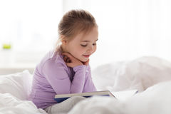 Happy little girl reading book in bed at home. People, childhood and bedtime concept - happy little girl reading book in bed at home Stock Image