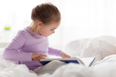 Happy little girl reading book in bed at home. People, childhood and bedtime concept - happy little girl reading book in bed at home Royalty Free Stock Photo