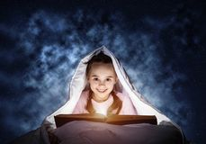Happy little girl reading book in bed royalty free stock image