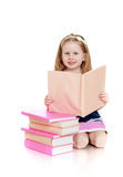Happy little girl reading a book on her knees Stock Image