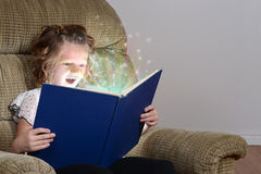 Happy little girl reading a book Stock Photos