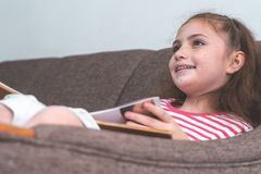 Happy Little girl reading book on sofa. Happy Little girl is reading book on sofa Royalty Free Stock Images