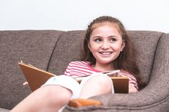 Happy Little girl reading book on sofa. Happy Little girl is reading book on sofa Royalty Free Stock Photo