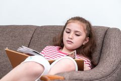 Happy Little girl reading book on sofa. Happy Little girl is reading book on sofa Royalty Free Stock Image