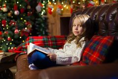 Happy little girl reading a story book by on the couch in a cozy Royalty Free Stock Photography