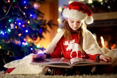 Happy little girl reading a story book by a fireplace in a cozy dark living room on Christmas eve Royalty Free Stock Images
