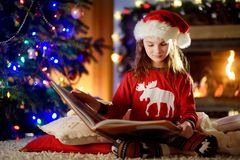 Happy little girl reading a story book by a fireplace in a cozy dark living room on Christmas eve Royalty Free Stock Photo